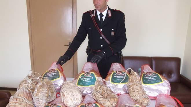 Un carabiniere mostra prosciutti e altri salumi rubati